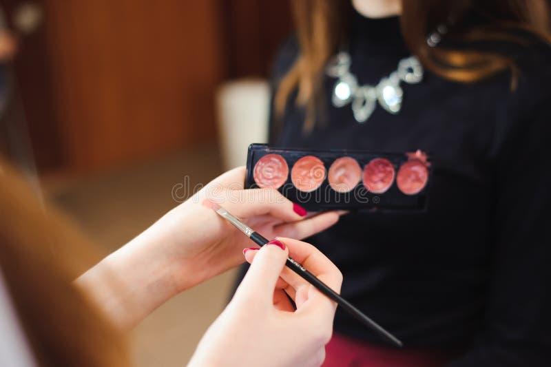 唇膏的构成汇集 设置装饰化妆用品在美发师的手上 免版税库存图片