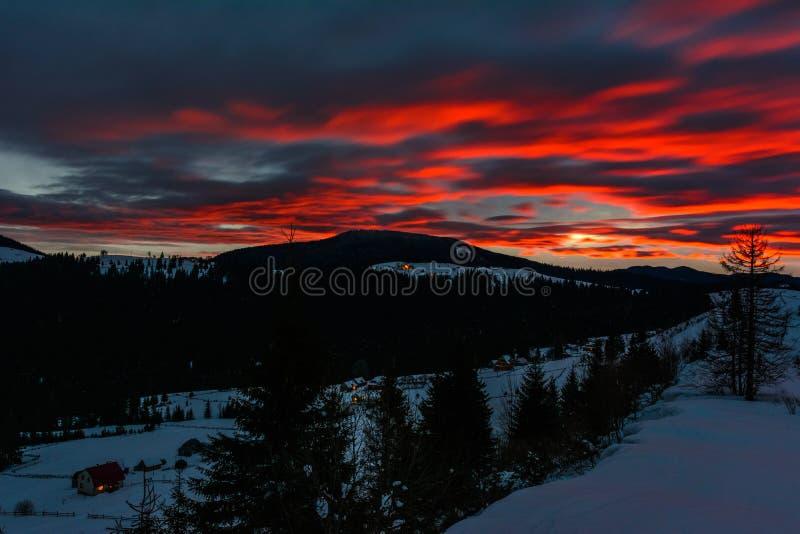 喀尔巴阡山脉的壮观的风景在与明亮的红色云彩的黎明 免版税库存照片
