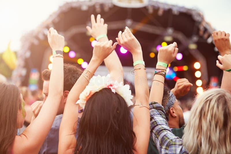 Åhörare med händer i luften på en musikfestival arkivbilder