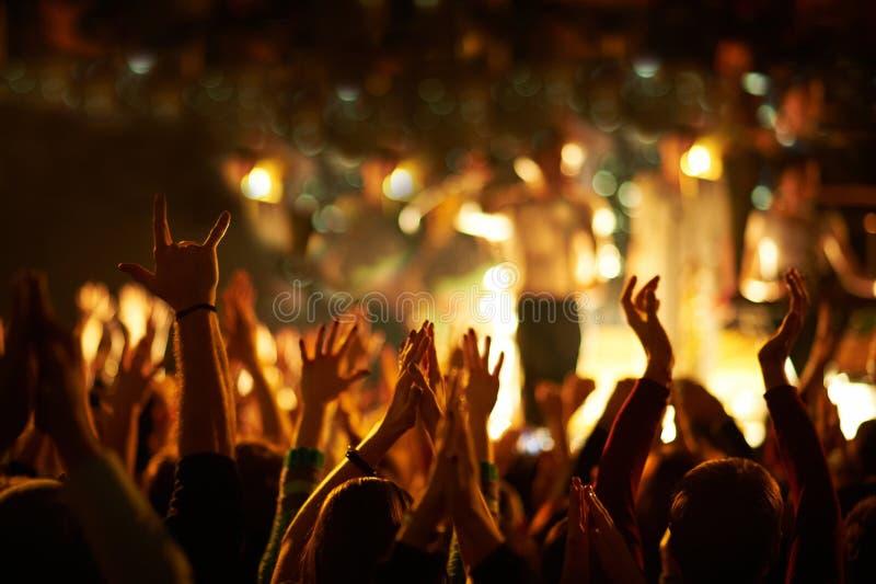 Åhörare med händer lyftte på en musikfestival och ljus som strömmar ner från ovanför etappen royaltyfria foton