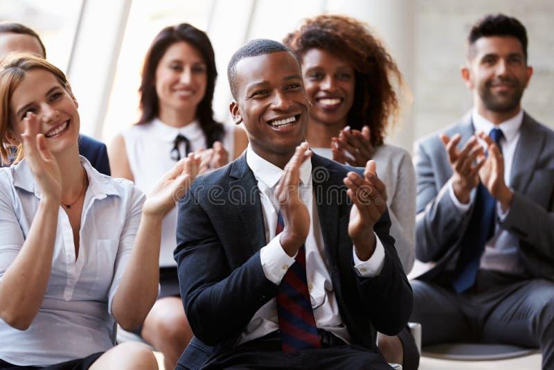 Åhörare som applåderar högtalaren på affärskonferensen arkivfoton