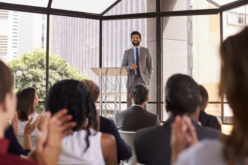 Åhörare som applåderar högtalaren på ett affärsseminarium arkivfoto