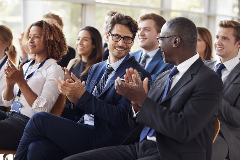 Åhörare som applåderar på affärsseminariet som ser de arkivfoton