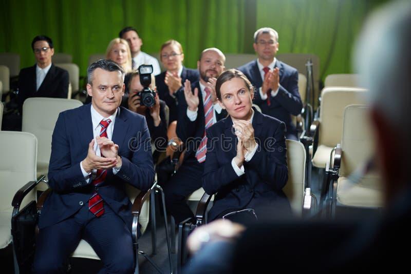 Åhörare som applåderar till högtalaren arkivfoto