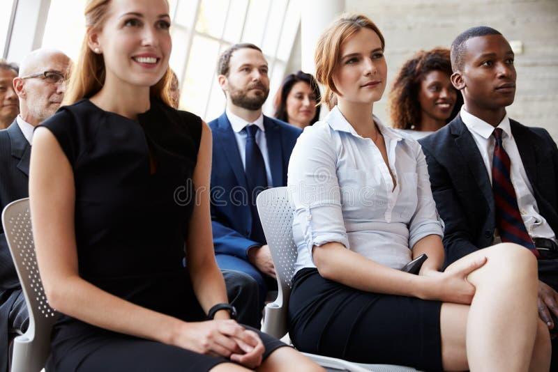 Åhörare som lyssnar till högtalaren på affärskonferensen royaltyfri foto