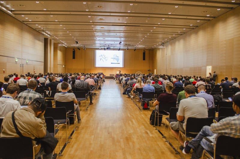 Åhörarefolk som betalar uppmärksamhet till en vetenskaplig presentation i en europeisk konferens royaltyfri fotografi