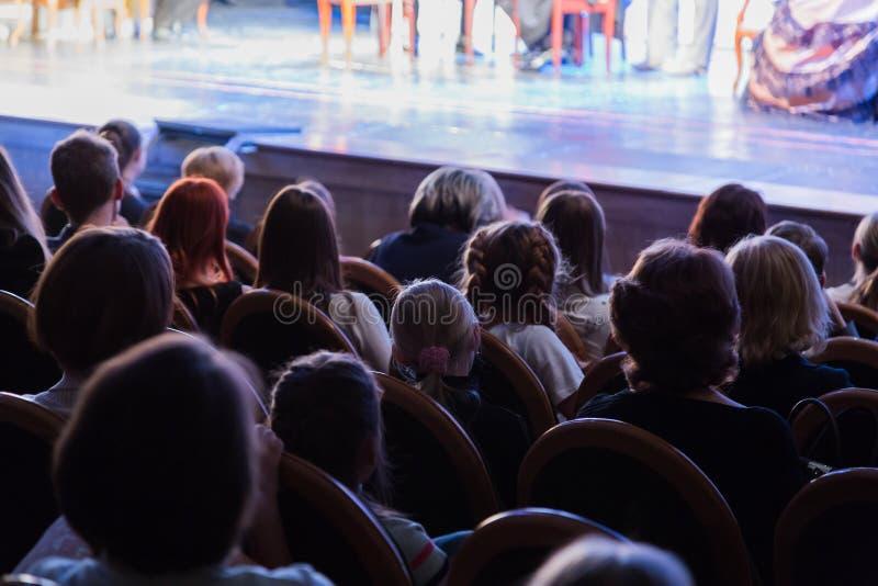 Åhörarna i teatern som håller ögonen på en lek Åhörarna i korridoren: vuxna människor och barn royaltyfri foto