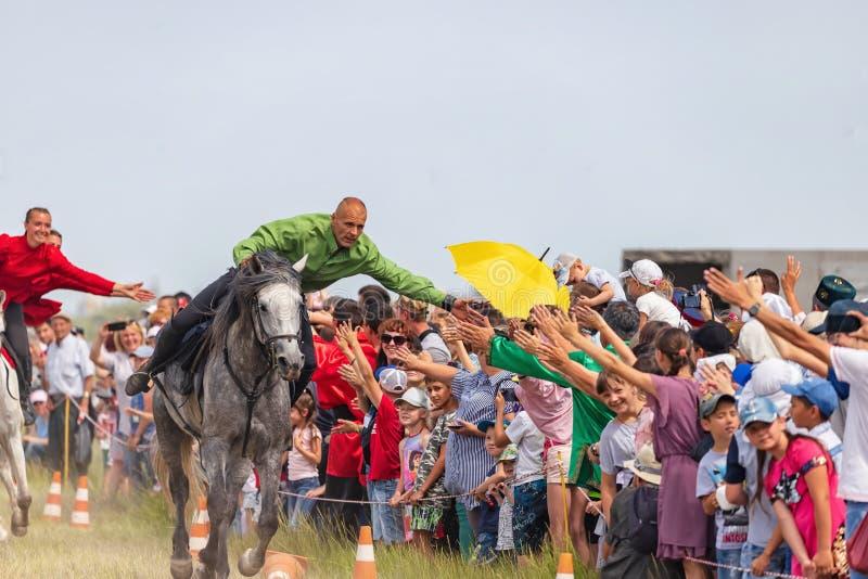 Åhörarna på festivalen av den Sabantuy välkomnandet och att tacka kosackarna för skärmen av jippon på hästrygg royaltyfria foton