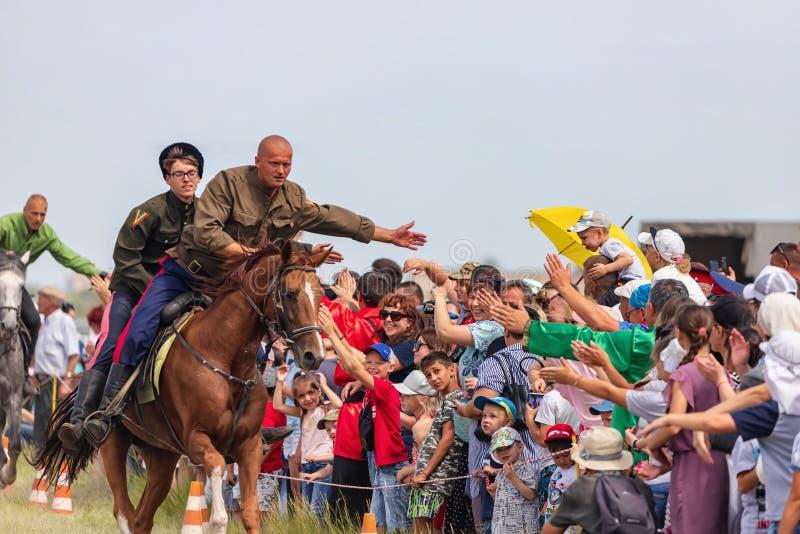 Åhörarna på festivalen av den Sabantuy välkomnandet och att tacka kosackarna för skärmen av jippon på hästrygg royaltyfria bilder