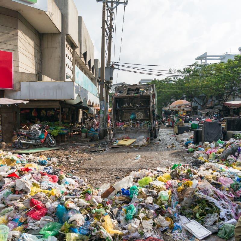 Åka lastbil rörande nedgrävning av soporavskräde, racka ner på på gatan arkivfoton