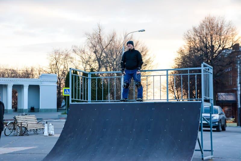 Åka skridskor för fritidsaktivitetmanrulle i centralen av staden på solnedgången Vinter royaltyfria foton