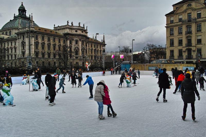 Åka skridskor jordning i stad på ganska jul arkivbilder