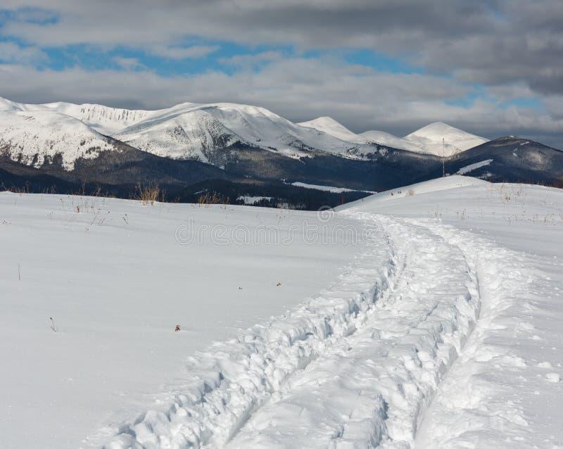 Åka släde spåret och fotspår på överkant för vinterbergkulle arkivbild