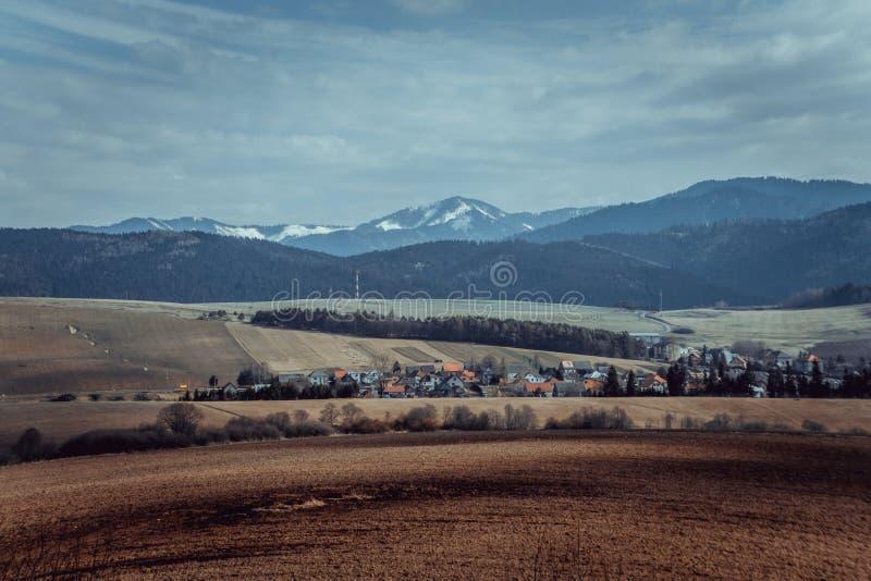 Åkerbrukt fält, härligt landskap med byn och berg royaltyfri foto