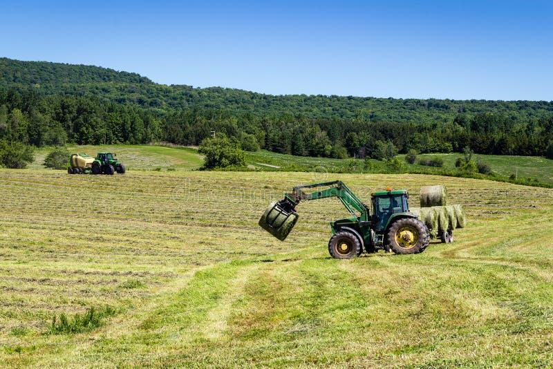 Åkerbrukt maskineri på höfält arkivfoto
