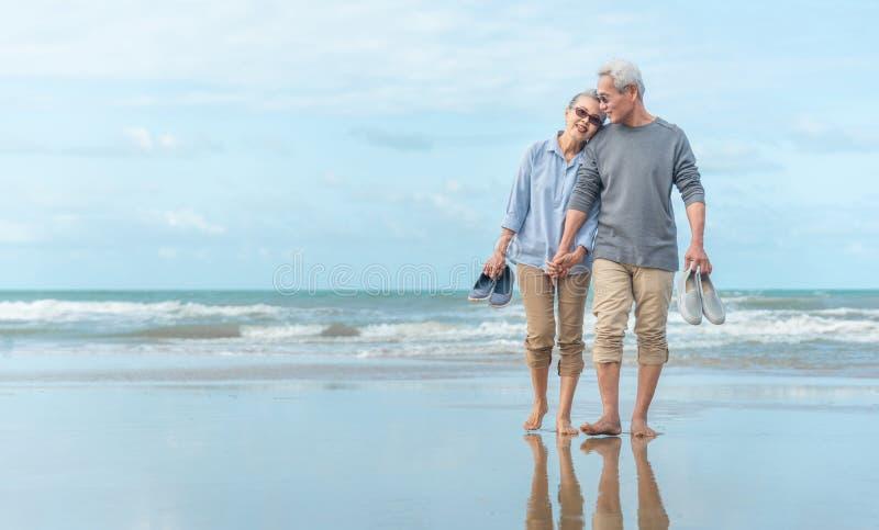 Ålder, resor, turism och människors uppfattning - lyckligt högt uppsatta par som håller hand och går på sommarstranden royaltyfri foto