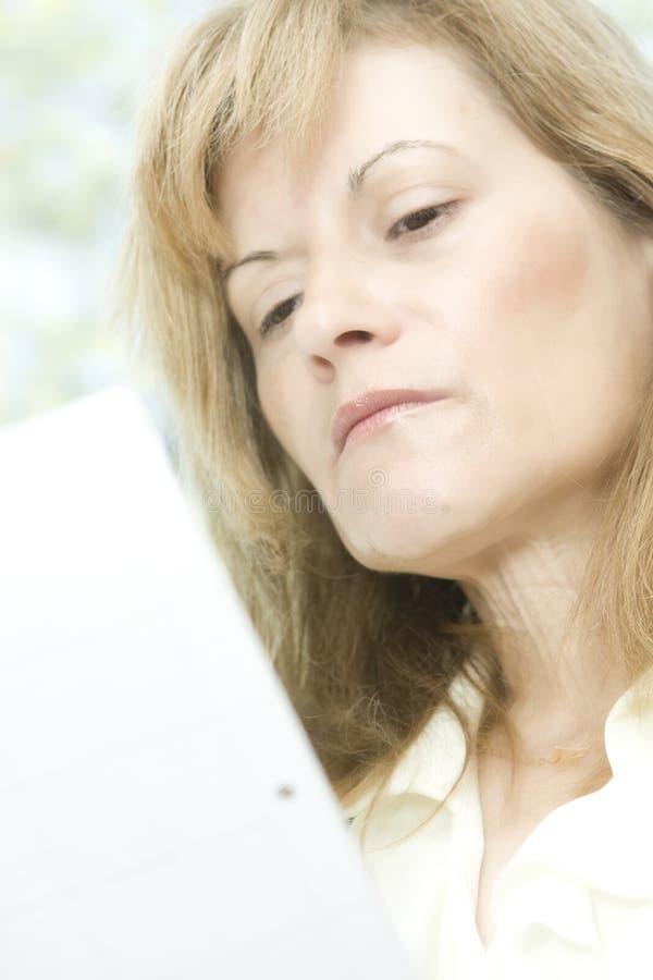 åldermedelavläsningskvinna royaltyfria foton