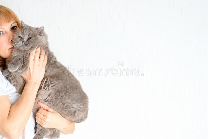 Åldrades den attraktiva mitt för ståenden kvinnan med katten fotografering för bildbyråer