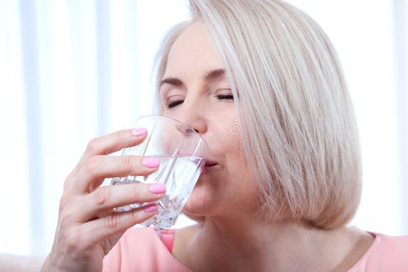 Åldrades den härliga mitt för ståenden kvinnadricksvatten i morgonen royaltyfri foto