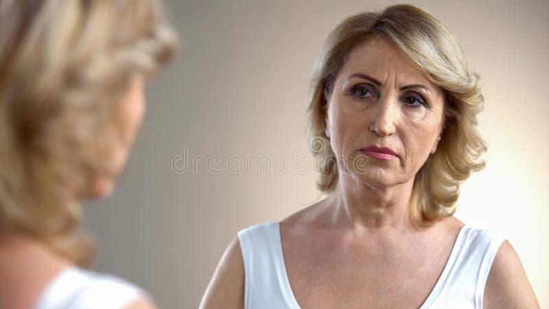 Åldras dam som ser i spegel på hennes rynkiga framsida som tänker om plastikkirurgi royaltyfri foto