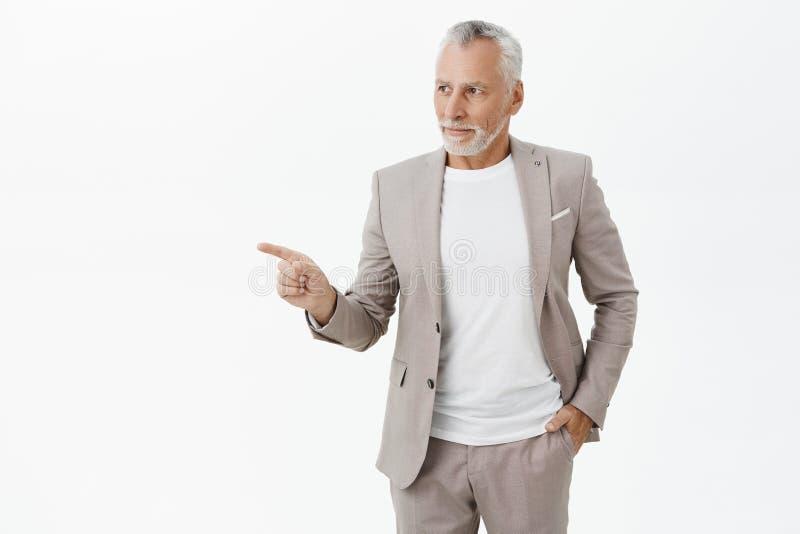 Åldras, folk och finansbegrepp Stående av den charmiga manliga entreprenören med grått hår och skägget i dräktinnehavhand arkivfoto