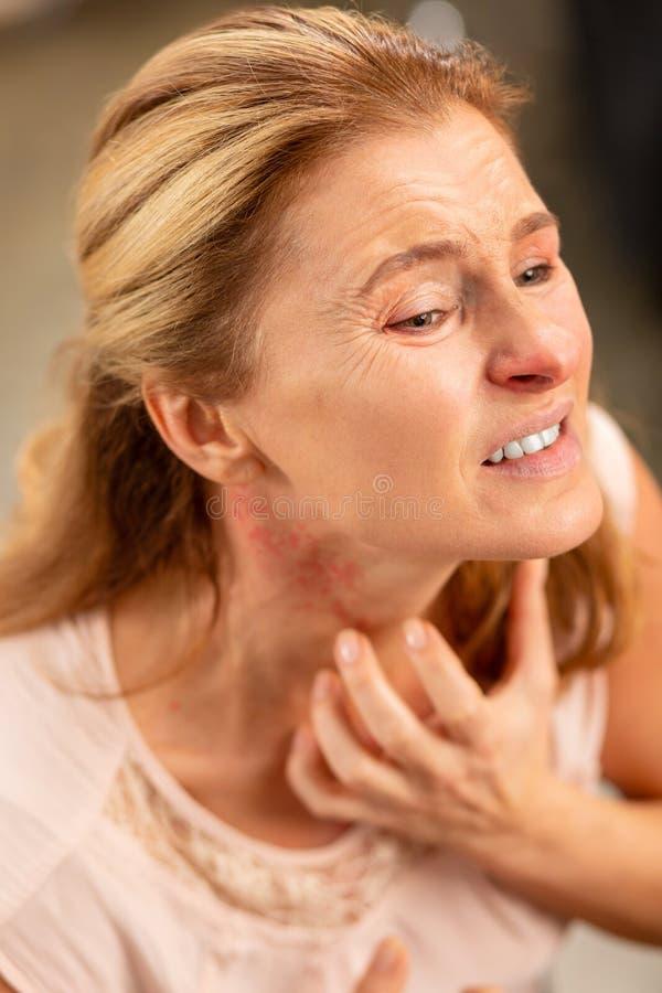Åldras kvinna som skrapar hennes hals, medan ha överilat och feber royaltyfria foton