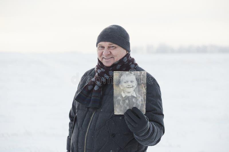 Åldras man med hans foto som barn royaltyfri foto