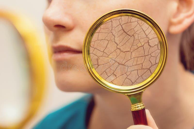 Åldras och torka framsidahudbegreppet - kvinna med förstoringsglaset royaltyfria foton
