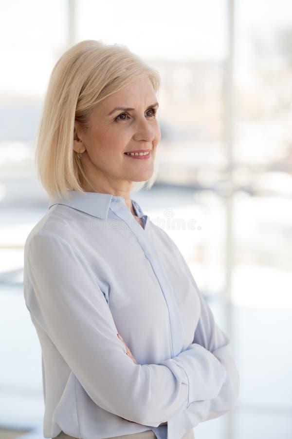 Åldrats attraktivt affärsdamanseende med händer som korsas på bröstkorg arkivfoto
