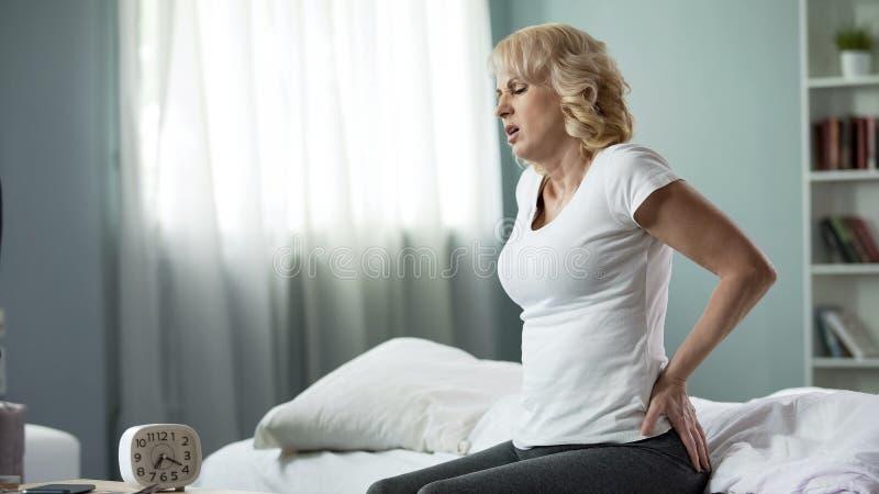 Åldrats kvinnalidande från låg baksida smärtar och att sitta på säng, den ryggrads- skivaherniationen fotografering för bildbyråer