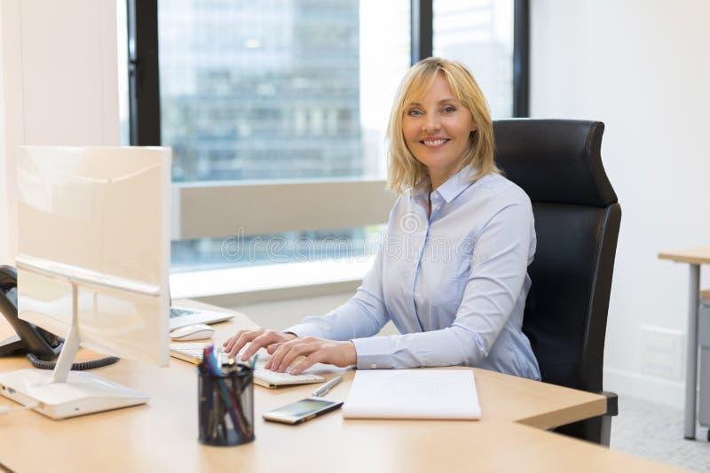 Åldrig affärskvinna för mitt som arbetar på kontoret royaltyfria foton