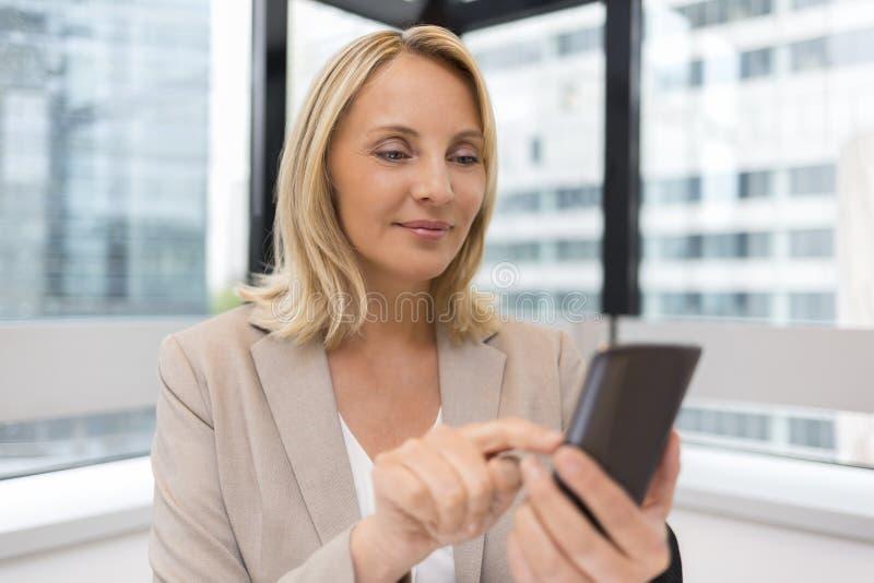Åldrig affärskvinna för mitt som arbetar på kontoret Använda Smartphone arkivbilder
