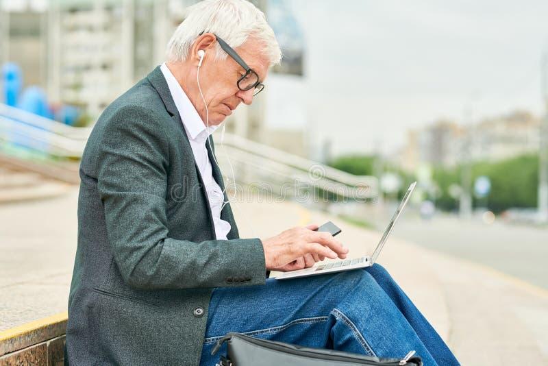 Åldrig affärsman som använder bärbara datorn och lyssnar till musik arkivbilder