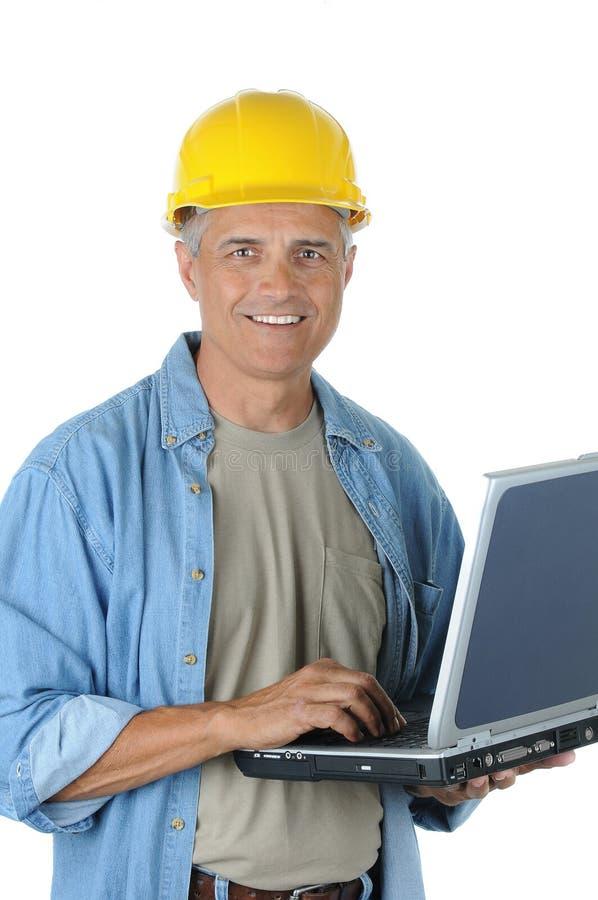 åldrig arbetare för mitt för konstruktionsholdingbärbar dator royaltyfri fotografi