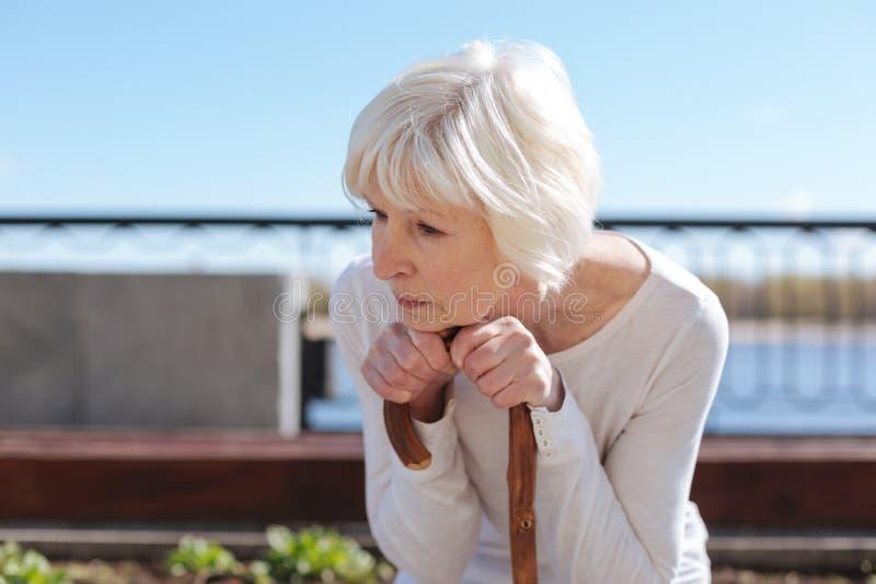 Åldrig dam som funderar på hennes framtid nära floden royaltyfria foton