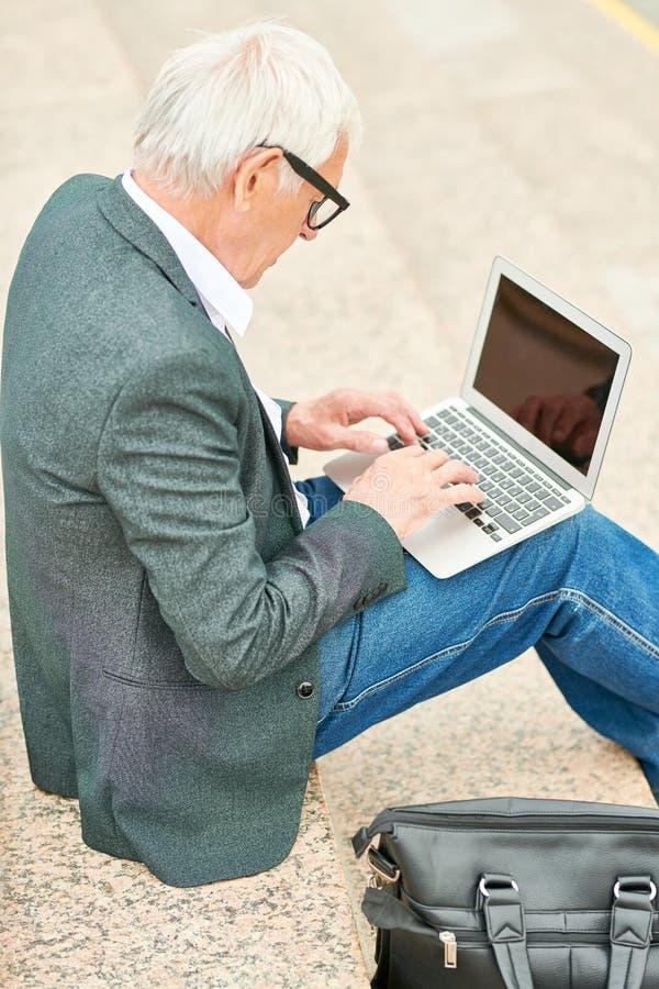 Åldrig entreprenör som använder bärbara datorn på moment royaltyfri fotografi