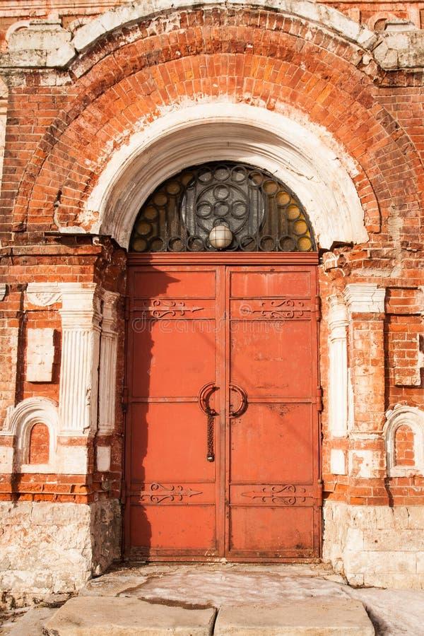 Åldrig gammal röd metalldörr med låset på gammal tegelstenfasad royaltyfri bild