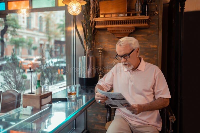 Åldrig grå färg-haired manläsningnyheterna i baren fotografering för bildbyråer