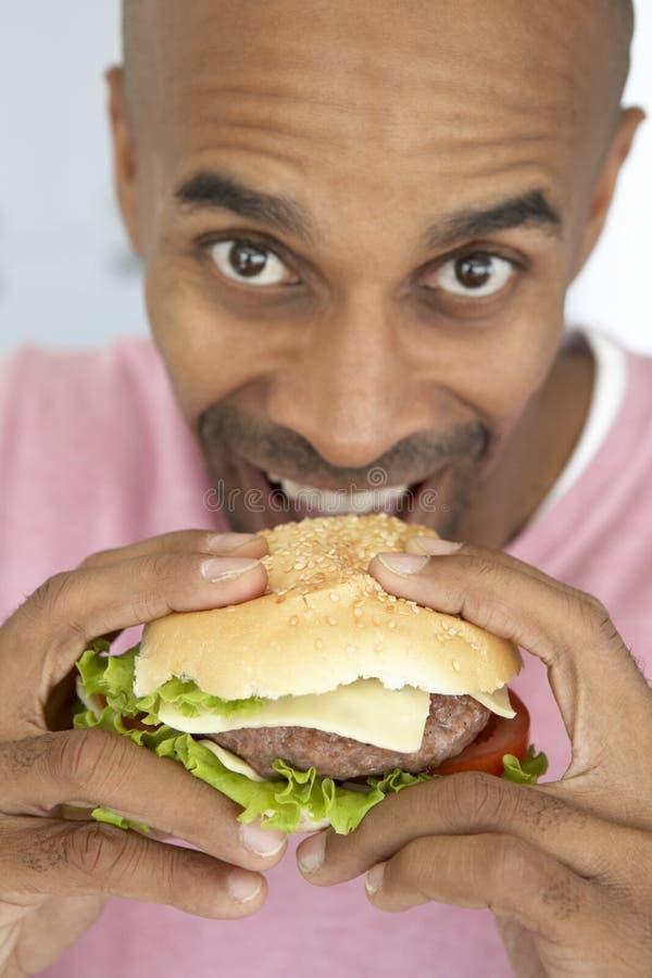 åldrig hamburgare som äter manmitten arkivfoton
