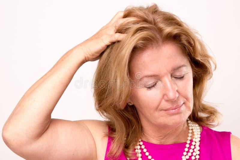 Åldrig kvinna för attraktiv mitt med en huvudvärk arkivfoto