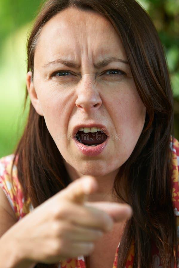 Åldrig kvinna för ilsken mitt som pekar på kameran royaltyfri bild