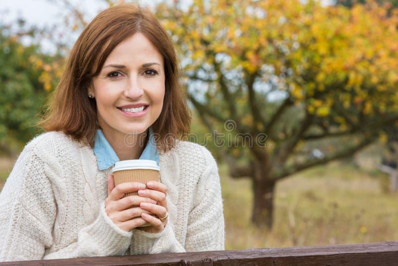 Åldrig kvinna för lycklig attraktiv mitt som dricker kaffe fotografering för bildbyråer
