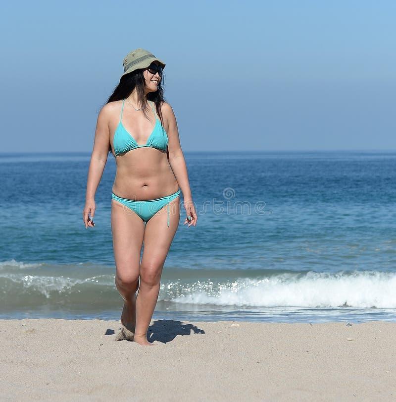 Åldrig kvinna för mitt på den sandiga stranden royaltyfria foton