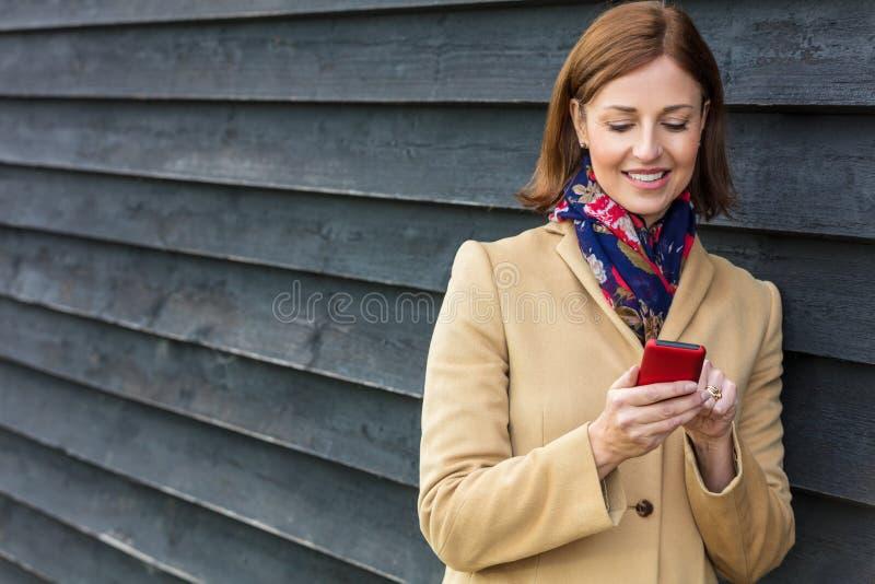 Åldrig kvinna för mitt som använder den mobila mobiltelefonen royaltyfri fotografi