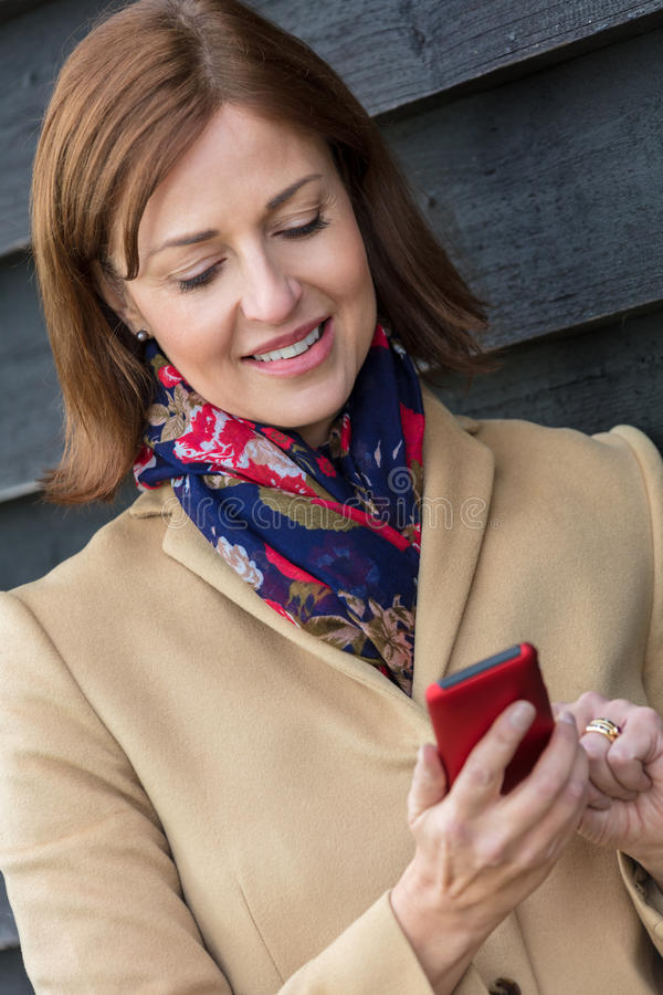 Åldrig kvinna för mitt som använder mobiltelefonen arkivbilder