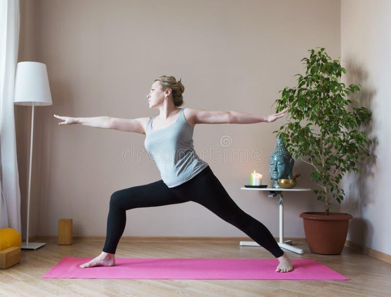 Åldrig kvinna för mitt som inomhus gör yoga arkivbild