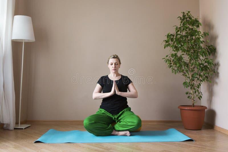 Åldrig kvinna för mitt som inomhus gör yoga arkivfoto