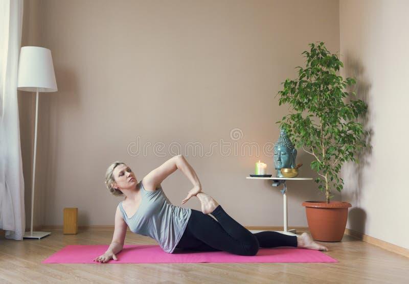 Åldrig kvinna för mitt som inomhus gör yoga royaltyfria foton