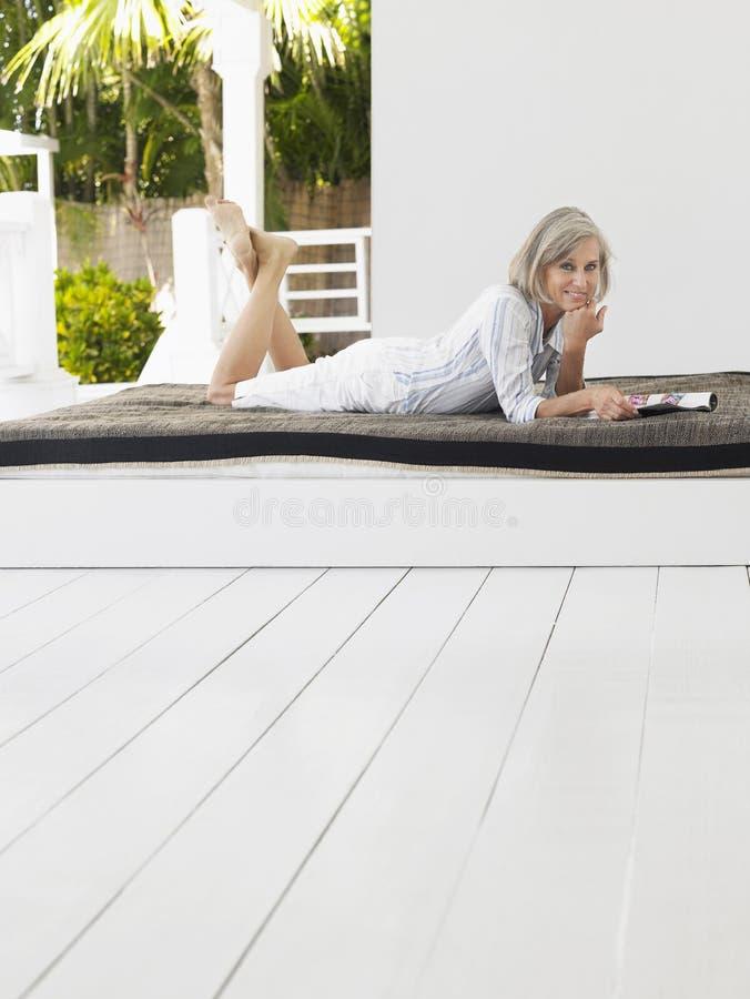 Åldrig kvinna för mitt som ligger på daybeden på veranda arkivfoto