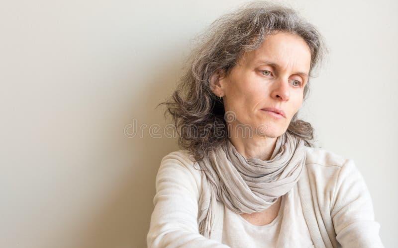 Åldrig kvinna för mitt som ser eftertänksam royaltyfri fotografi